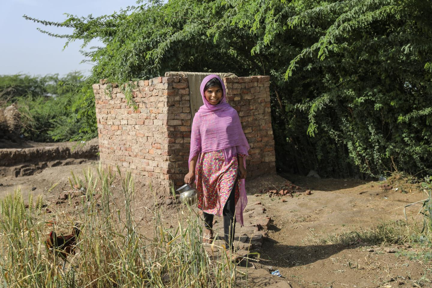 Zahra walks out after using the newly constructed latrine