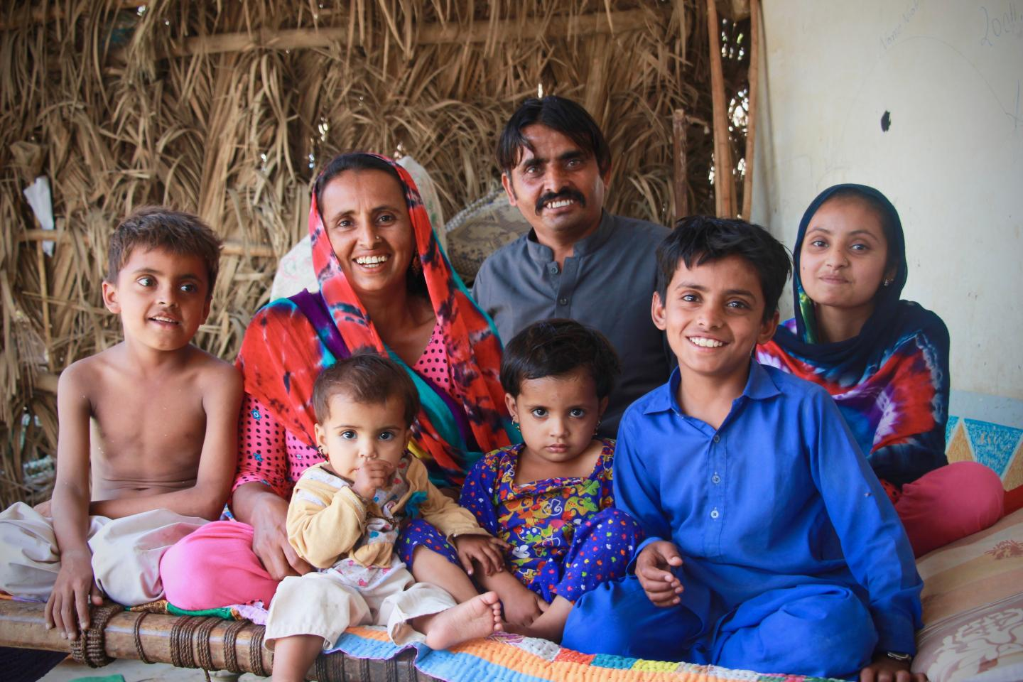 A village family from Sindh province, Pakistan looks at the camera as they enjoy some family time on a hot summer day.