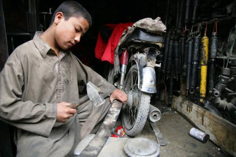 A boy repairs a motorcycle