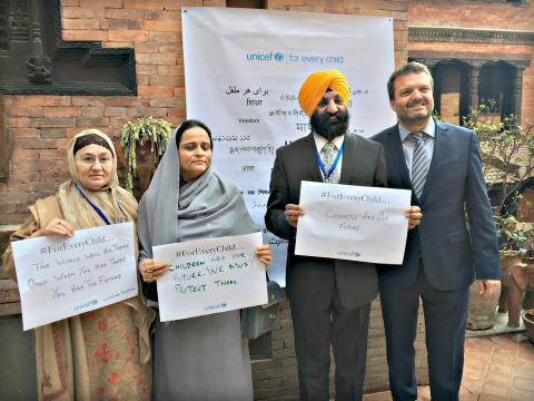The image shows a delegation of Pakistani parliamentarians with a UNICEF staff member standing with their child rights hopes written on placards