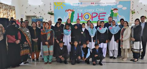 The image shows students and teachers posing after an art contest