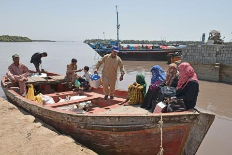 Vaccinators sitting in a boat which will take them to island settlements around Karachi