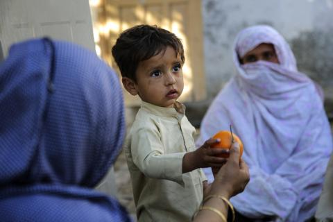 Lady health worker Sajjda Bibi giving a fruit to a child