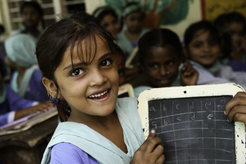 The image shows a girl writing on a small blackboard