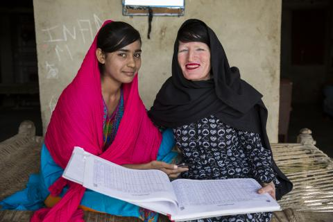 A lady health worker smiles as she sits with her daughter