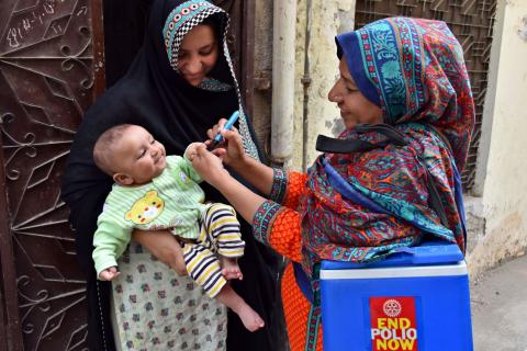 A frontline worker vaccinates a child against polio