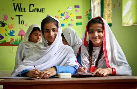 Sumair and Zainab smile in their classroom