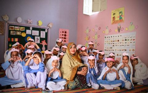 Zeenat sits with students in her class