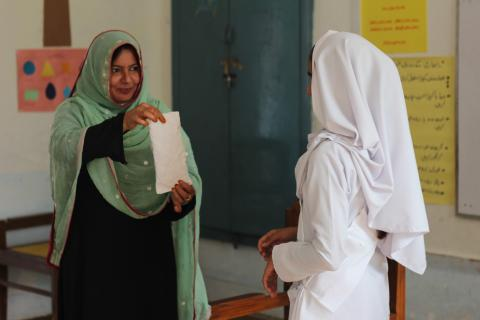 A female teacher shows a sanitary pad to a girl student during an MHM awareness session
