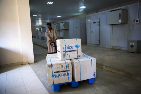 A man transports vaccines in a warehouse