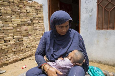 The image shows a woman breastfeeding her baby