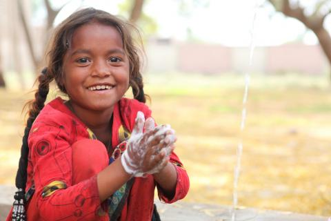 a young girl washes hands