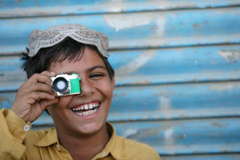 A boy plays with a toy camera