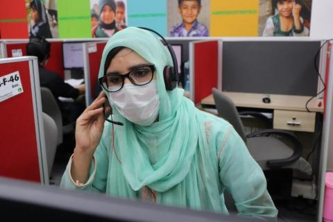 A woman answers a call in the call centre