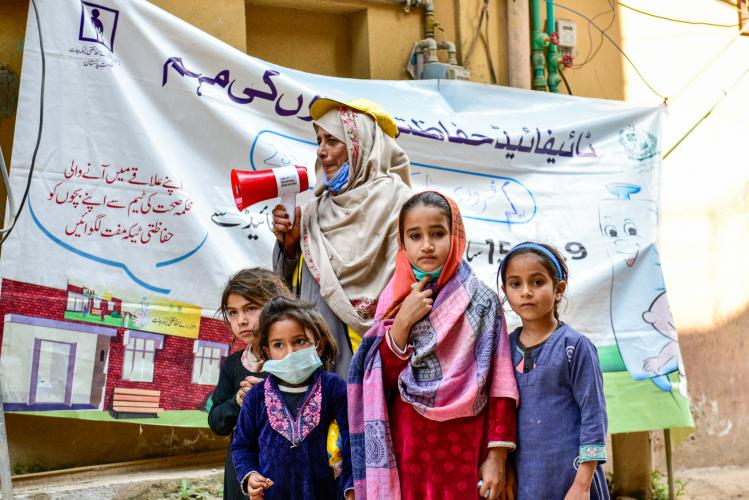 Children gather around Tahira Parveen, a Lady Health Worker, as she calls on parents to bring their children to the vaccination point on the streets of Dhok Nizam, an urban informal settlement in Islamabad