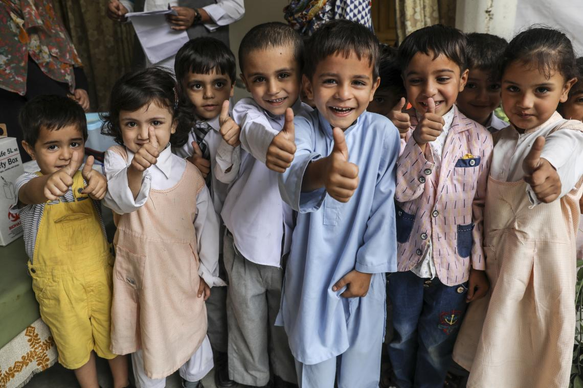 smiling school children give a thumbs up to the camera