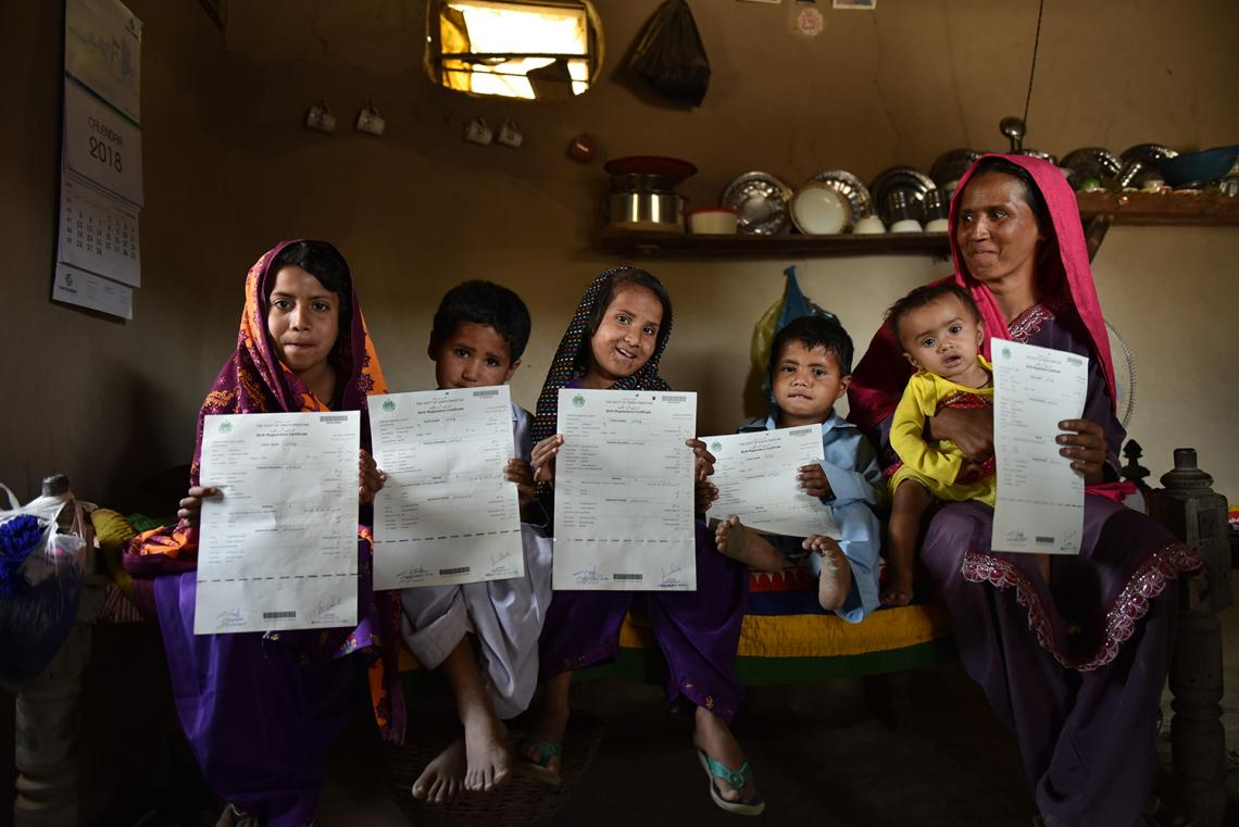Zahida and her children holding their birth certificates