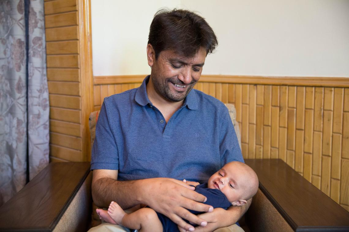 The image shows a father hokding his infant son in his arms