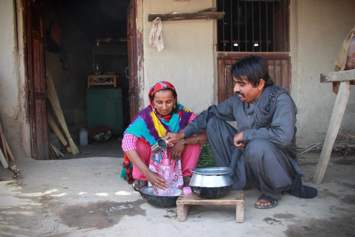 A husband and wife making dinner preparations for the family in a village in Sindh, Pakistan.