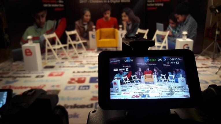 The image shows a studio set up for a panel discussion