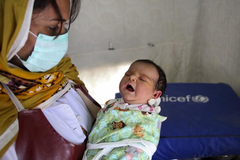 A lady health worker holds a newborn baby