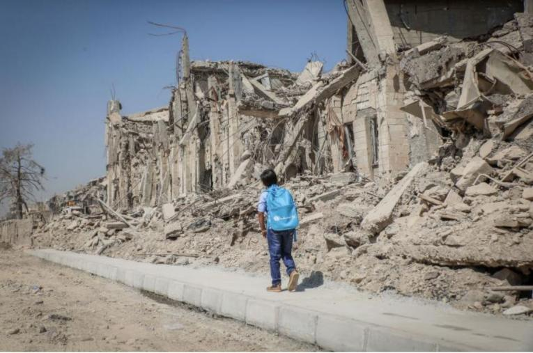 A child walks past a rubble of a damaged building
