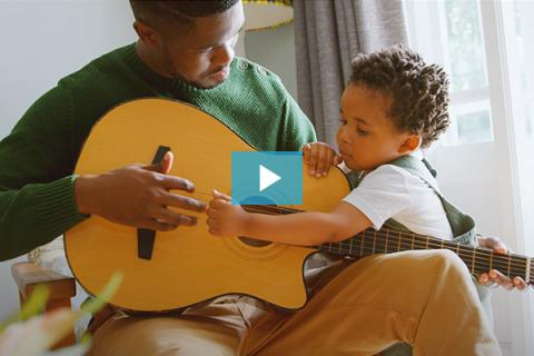 A father plays guitar with his child.