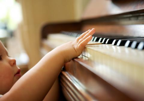 A toddler reaches up to touch keys on a piano.