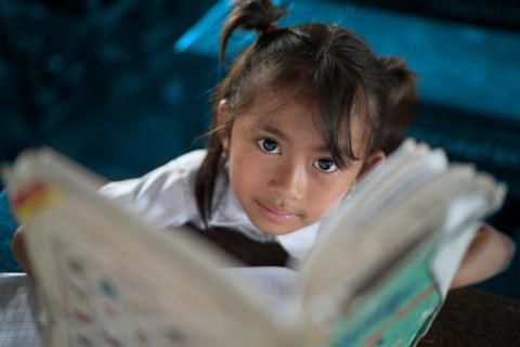 Cambodia. A child holds up a book.