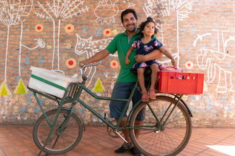 Parenting in Paraguay: a father holds his 2-year old daughter atop the bicycle that serves as the family's transportation and mobile food-sales cart