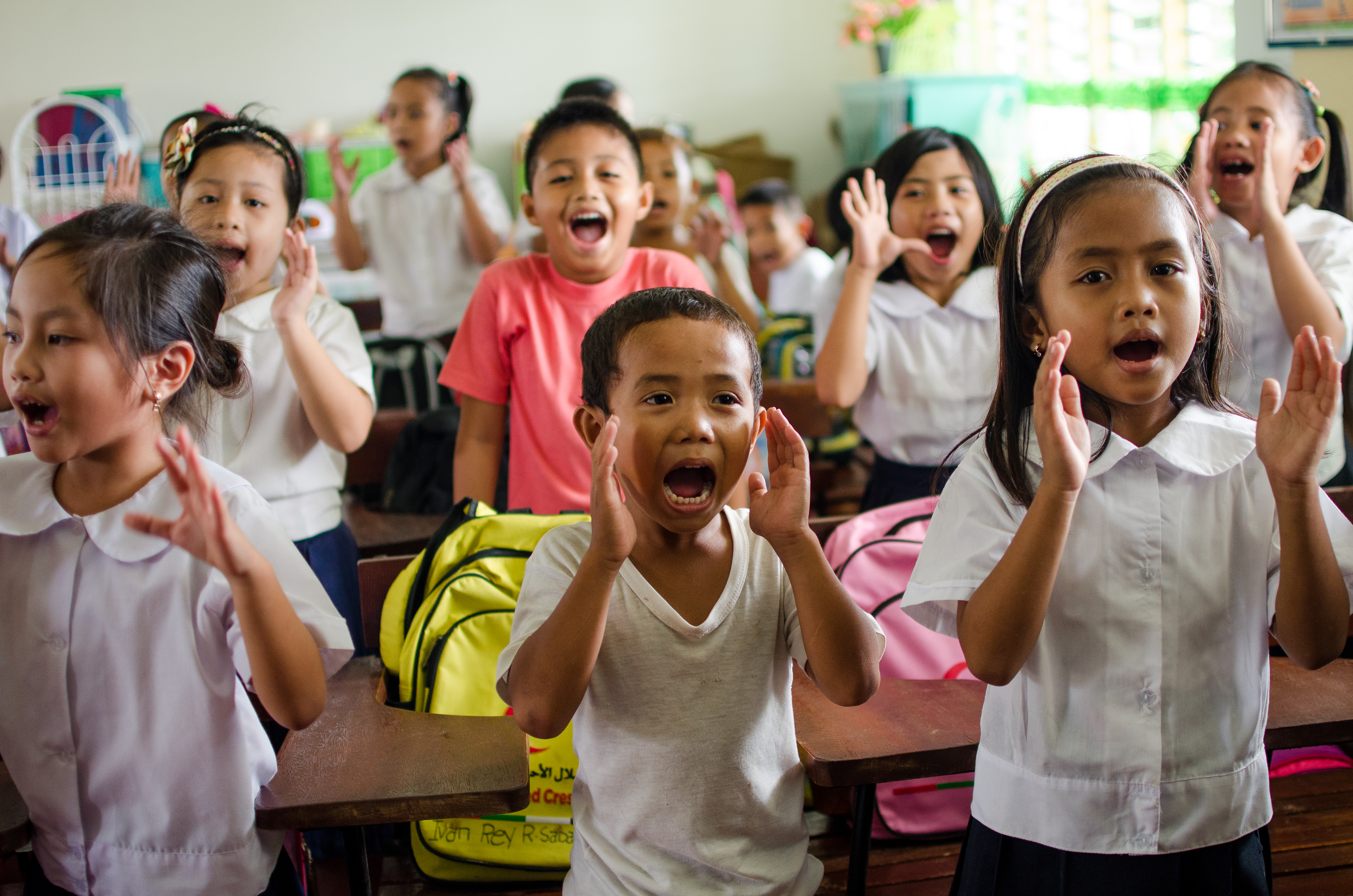 Children stand up and and yell during a class activity inside a classroom