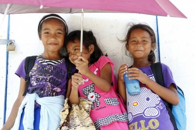 Three children carrying school bags gather under an umbrella, smiling