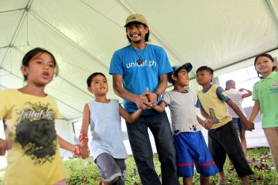 A UNICEF staff member, wearing a blue UNICEF t-shirt with the URL for the UNICEF Philippines website, holds hands with children participating in a recreational activity inside a UNICEF tent.