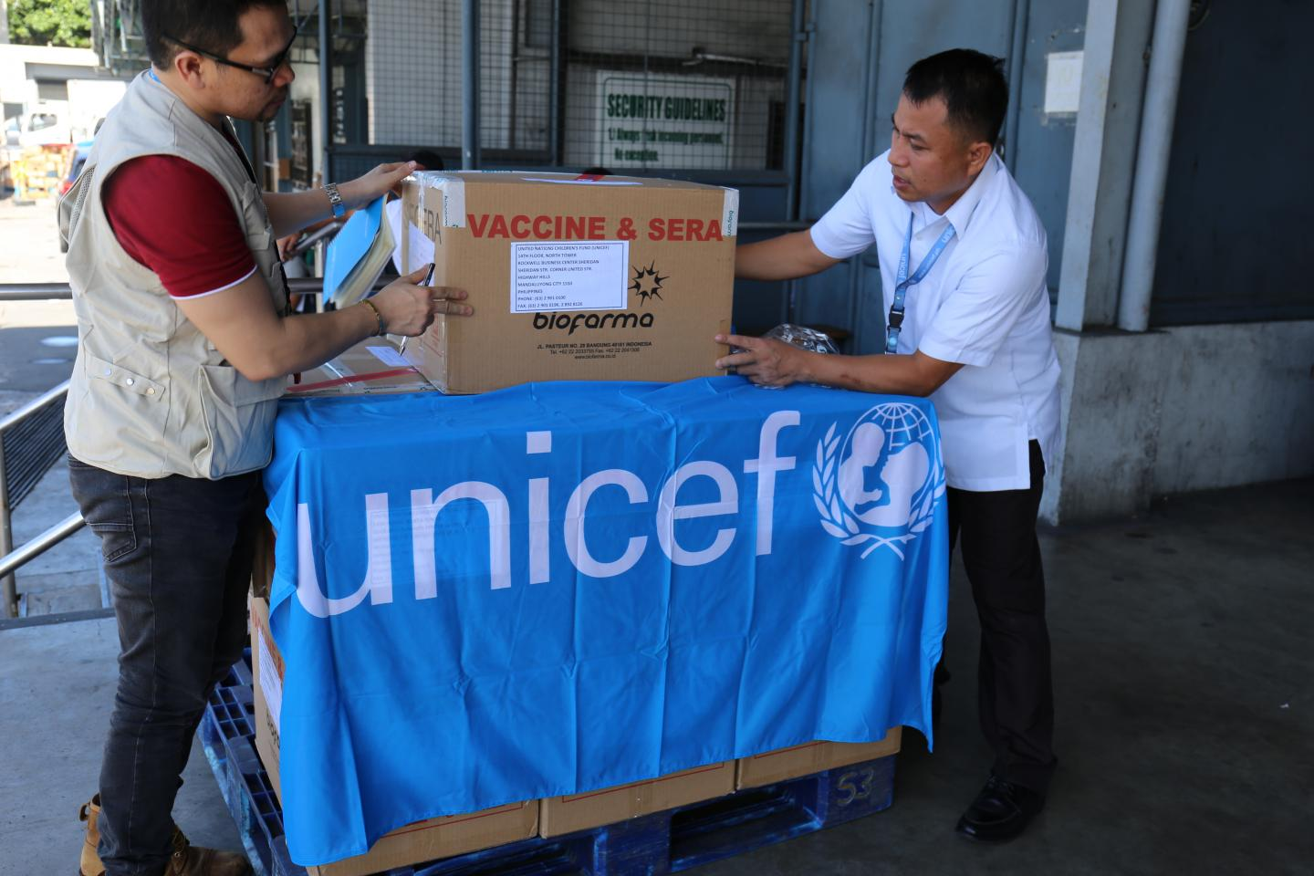 UNICEF staff inspect boxes of polio vaccines