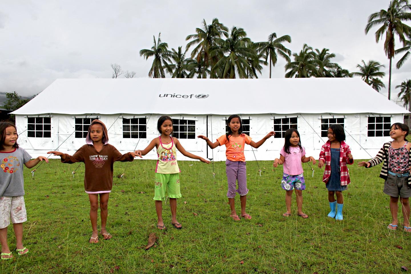 Children playing in front of a UNICEF tent