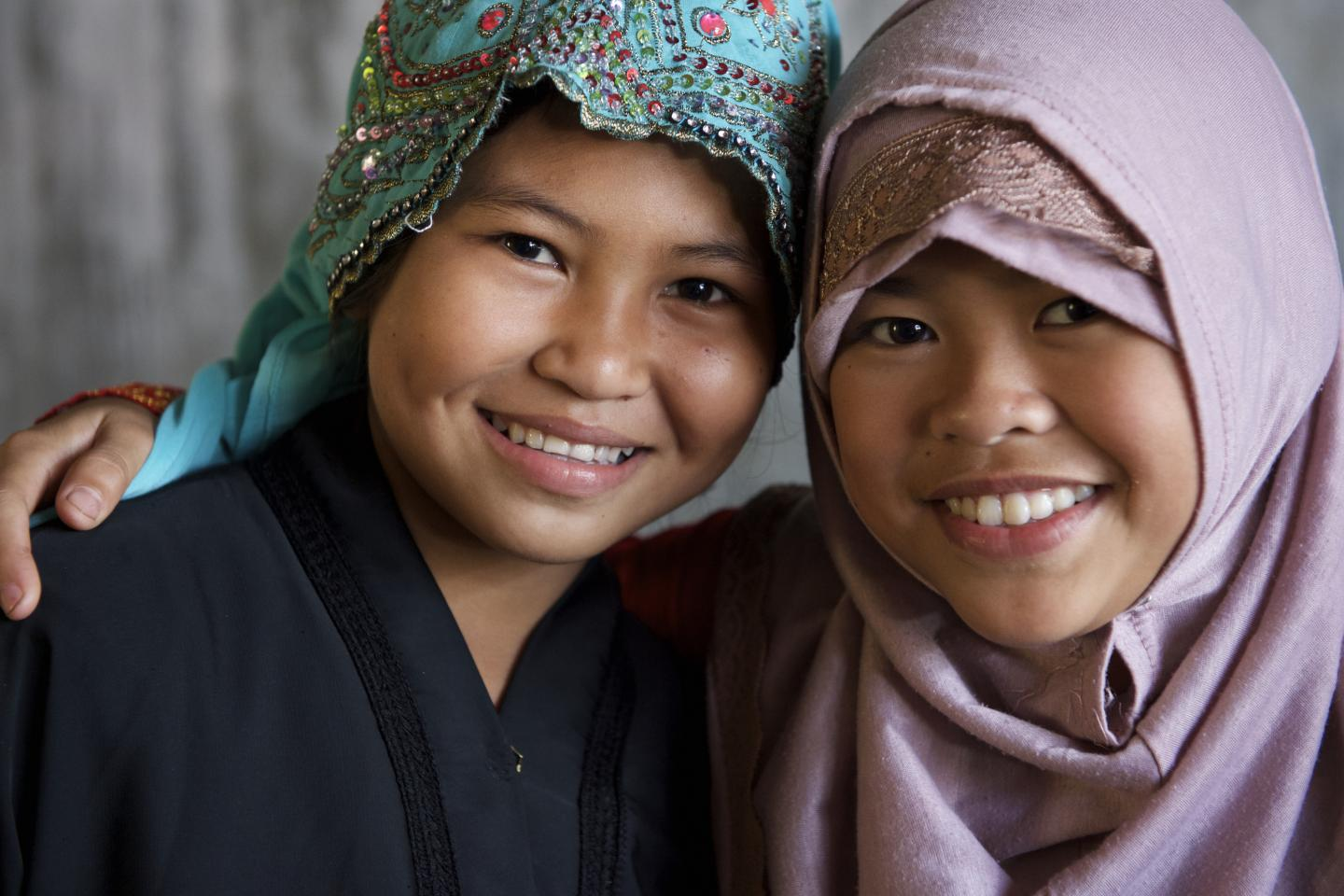 Two girls wearing hijabs smile in front of the camera