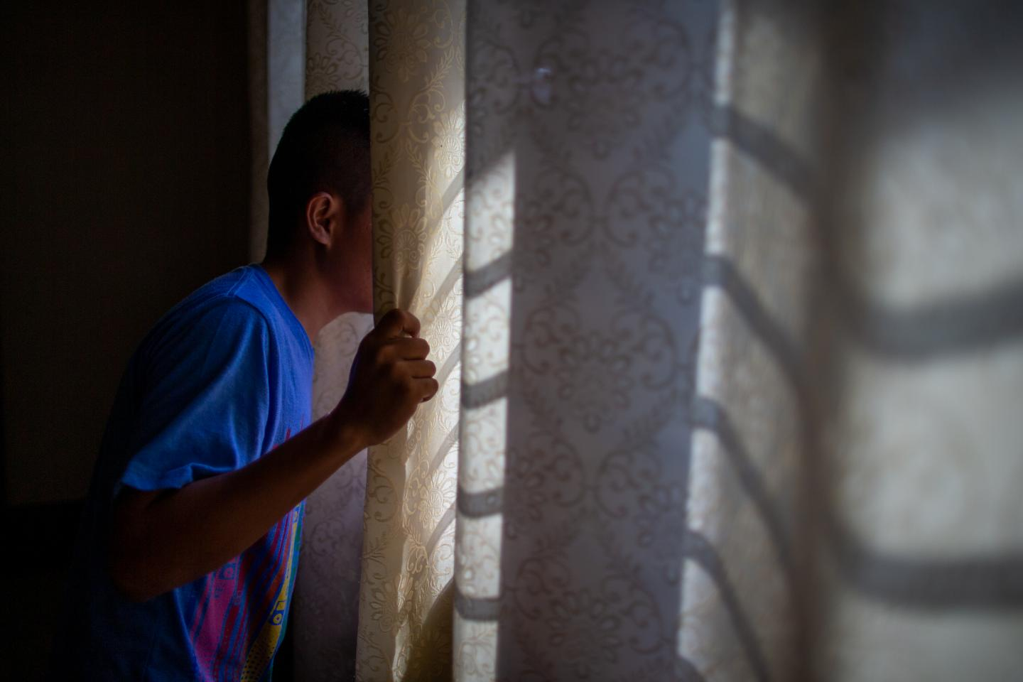 A child in a blue shirt looks out of a window, the curtain hiding his face
