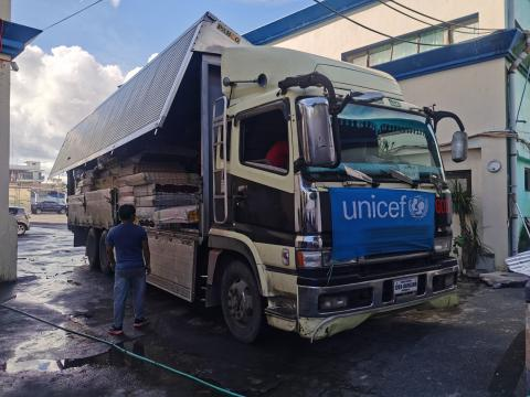 A truck carrying UNICEF supplies, with a UNICEF banner in front