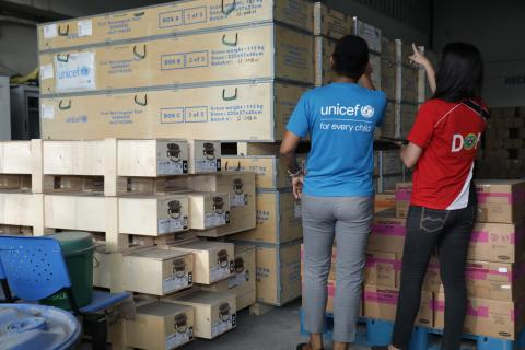 Staff members from UNICEF and the Department of Health, wearing their respective branded shirts, inspect UNICEF tents delivered to the Department of Health warehouse