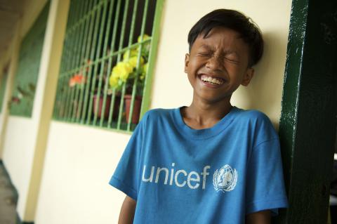 A boy in a blue UNICEF shirt smiling towards the camera with his eyes closed