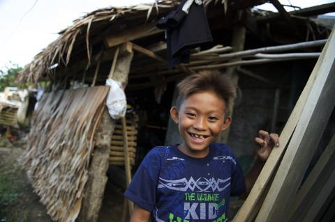 A smiling boy stands outside a hut