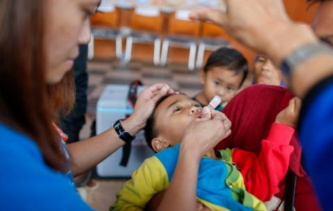A child receives a dose of oral polio vaccine