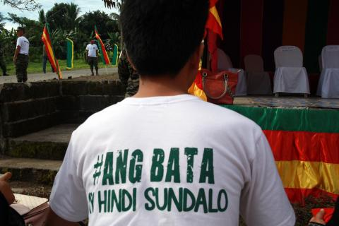 "A boy, wearing a shirt printed with ""Ang bata ay hindi sundalo"" (a child is not a soldier) with his back faced toward the camera"
