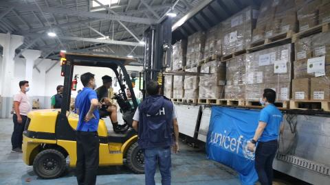 Warehouse staff unloading UNICEF supplies