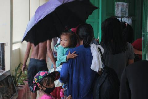 Families take temporary shelter at Albay Central School in Legazpi City ahead of Typhoon Ulysses' landfall