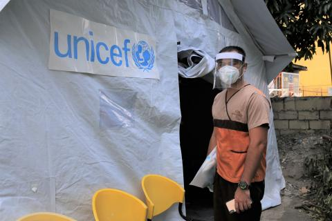 A health worker wearing a protective face shield and face mask stands outside a UNICEF tent
