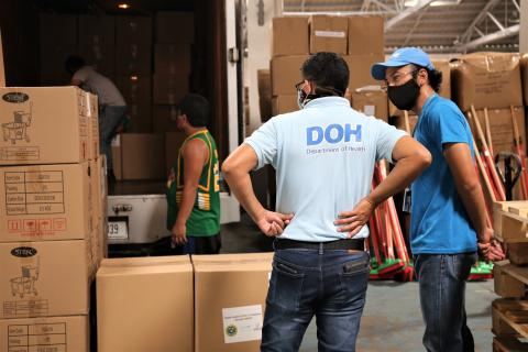 Two staff members from UNICEF and the Department of Health, both wearing shirts branded with their respective agency logos, inspect a delivery of supplies in a warehouse