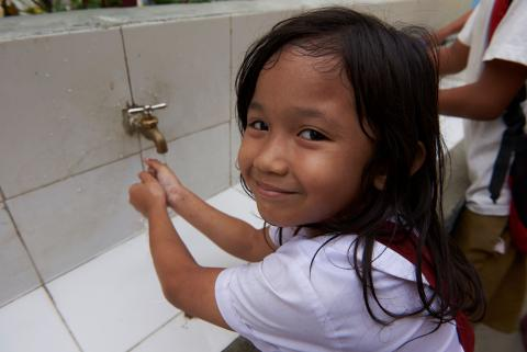 Iris smiles washing her hands using soap and water outside her classroom