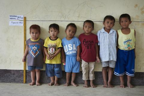 Children with different heights but of the same age line up in front of a height measurement line