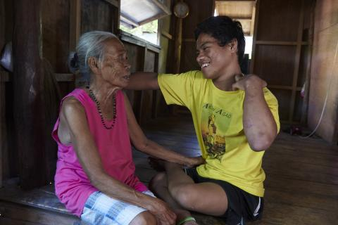 A woman and her grandson speaking to each other at their home